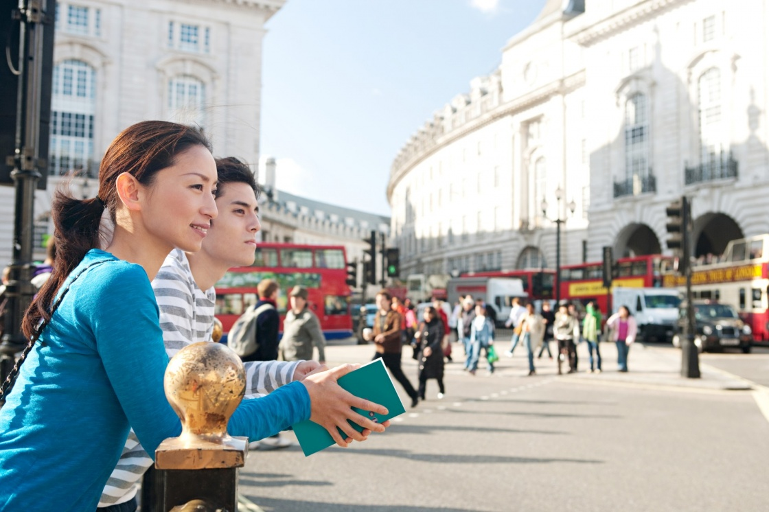 'Side portrait view of a young Japanese tourist couple in Piccadilly Circus landmark street with red buses, while visiting the city of London on holiday, smiling during a sunny day outdoors.' - Λονδίνο